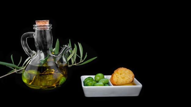 Puro olio vergine di oliva con olive, rami di ulivo, olio e pane su una superficie scura