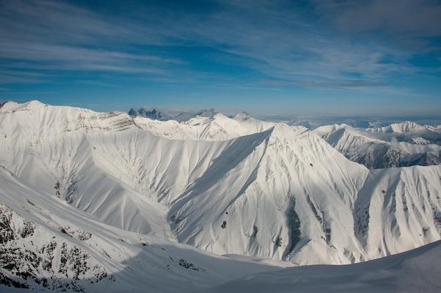 Montagne pure di inverno coperte di neve sotto il cielo blu luminoso