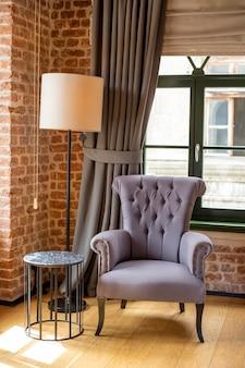 La poltrona viola si trova vicino alla finestra e al tavolo da tè in una stanza con pareti di mattoni rossi