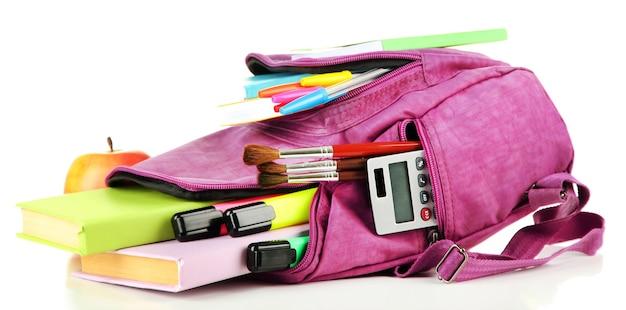 Zaino viola con materiale scolastico isolato su bianco