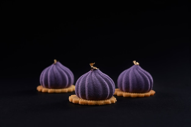 Torte viola con superficie opaca isolata sul nero.
