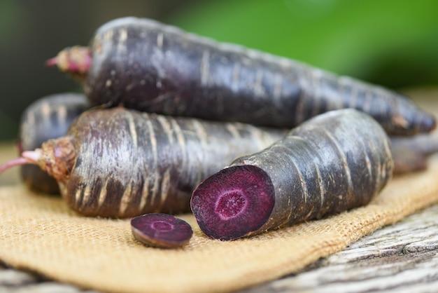 Carota viola sul sacco, carota fresca per cucinare vegetariano sulla tavola di legno