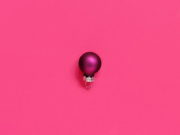 Pallina di natale viola su sfondo rosa