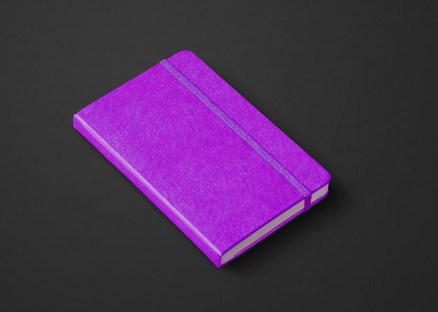 Modello di taccuino chiuso viola isolato su nero
