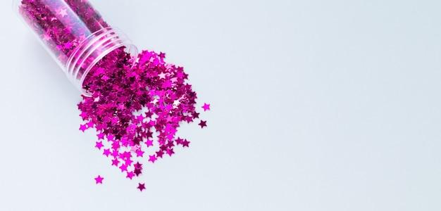 Coriandoli viola che cadono dalla bottiglia di vetro, materiale per decorazioni fai da te o per le vacanze