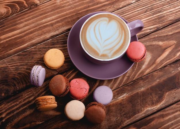 Tazza di caffè viola con cuore e amaretti colorati sullo sfondo in legno vista dall'alto