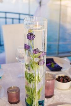 L'eustoma porpora fiorisce in una boccetta di vetro del vaso su un banchetto festivo