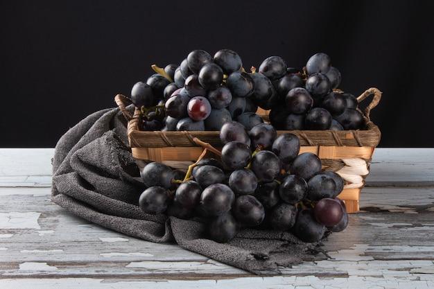 Cestino di uva da frutta viola su legno invecchiato e superficie nera.