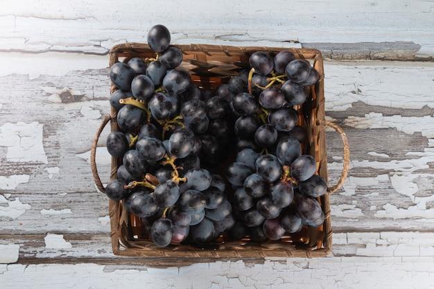 Merce nel carrello porpora dell'uva della frutta sulla superficie di legno invecchiata.