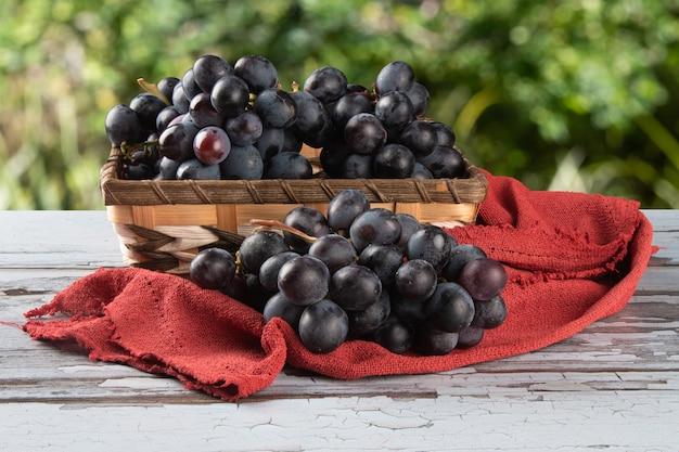 Merce nel carrello porpora dell'uva della frutta con superficie verde vaga.