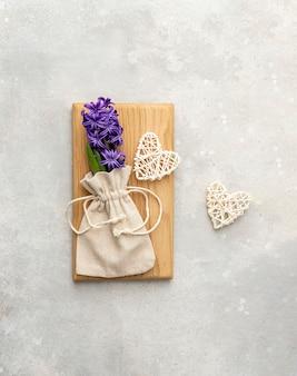 Giacinto viola in un sacchetto di lino e cuori intrecciati fatti a mano su uno sfondo grigio.