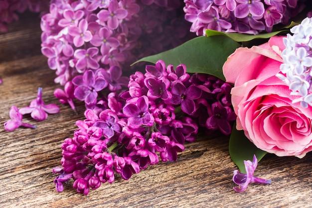 Fiori lilla viola con rose rosa sulla fine del tavolo in legno