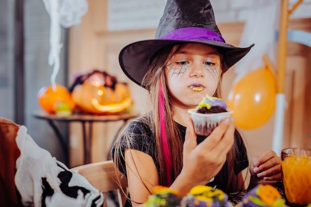 Labbra viola. divertente carina ragazza dai capelli scuri con labbra viola e gialle che indossa il vestito di halloween che mangia cupcake luminoso