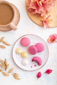 Macarons viola o torte di amaretti con una tazza di caffè su uno sfondo di cemento bianco decorato con fiori.