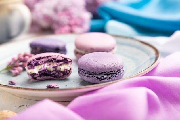 Macarons viola o torte di amaretti con una tazza di caffè su uno sfondo di cemento bianco e tessuto magentablue. vista laterale, primo piano,