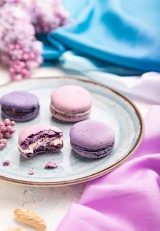 Macarons viola o torte di amaretti con una tazza di caffè su una superficie di cemento bianco e tessuto blu magenta