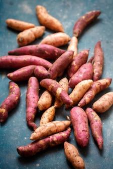 Patate dolci viola e arancioni su sfondo turchese