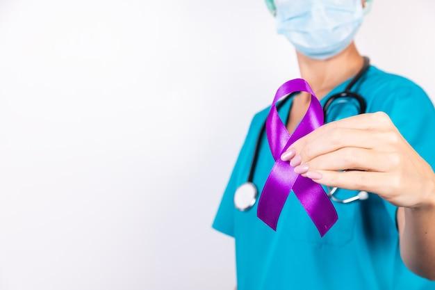 Nastro viola in un cancro al pancreas della mano femminile, simbolo di epilessia su un bianco