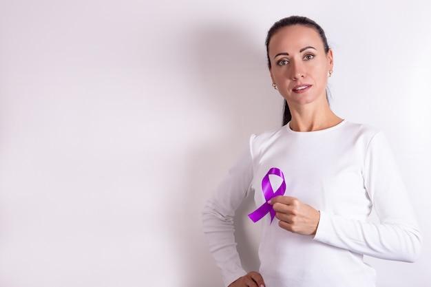 Nastro viola in un simbolo di cancro al pancreas mano femminile su sfondo bianco