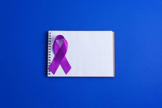 Nastri viola e quaderno aperto, morbo di alzheimer, cancro del pancreas, consapevolezza dell'epilessia, consapevolezza della violenza domestica,