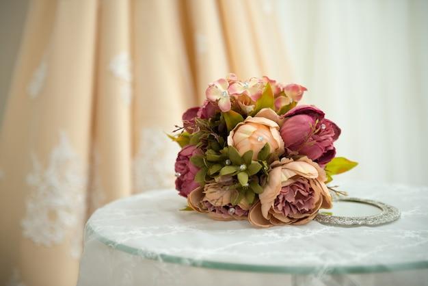 Bouquet di rose viola per la sposa nel suo giorno speciale. bouquet da sposa di fiori sul tavolo con pizzo