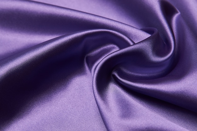 Sfondo viola tessuto di seta, primo piano. la trama liscia del panno di raso viola può essere utilizzata come sfondo astratto con lo spazio della copia