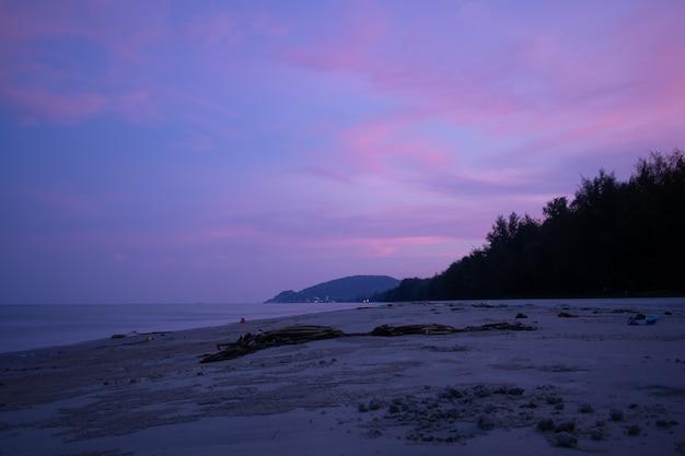 Cielo viola con fascio di luce dal tramonto sulla spiaggia sporca.