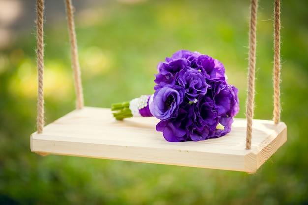 Bouquet da sposa viola su una bellissima altalena e
