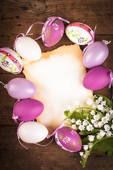 Uova viola e bianche e biglietto di auguri vuoto. decorazioni pasquali