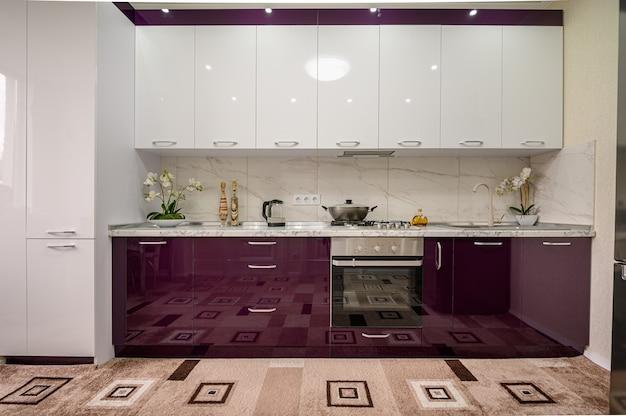 Cucina moderna viola e bianca interni progettati in stile minimalista, vista frontale alla facciata