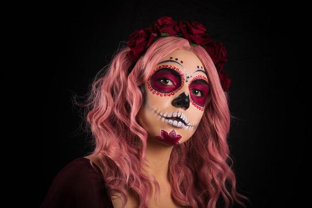 Sfere di plastica viola, gialle, blu. donna con trucco del cranio dello zucchero e capelli rosa isolati. giorno della morte.