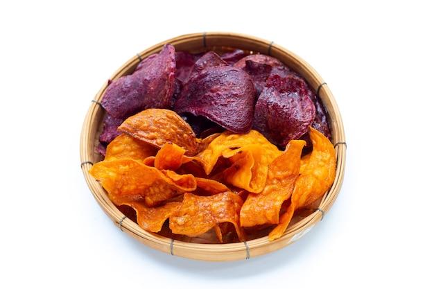 Patatine fritte porpora e gialle della patata dolce in canestro di bambù su fondo bianco.