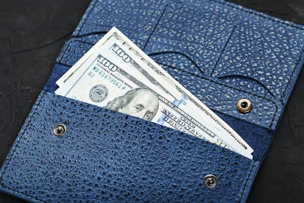 Borsa di colore blu in vera pelle con nuove banconote da cento dollari su un muro nero.