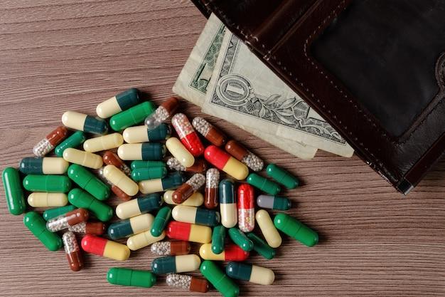 Una borsa con dentro un dollaro si trova su un tavolo di legno accanto a un mucchio di pillole sparse.