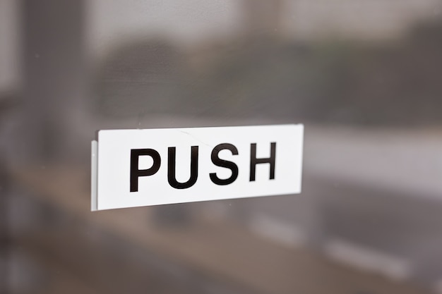 Cartello push su porta in vetro. push iscrizione