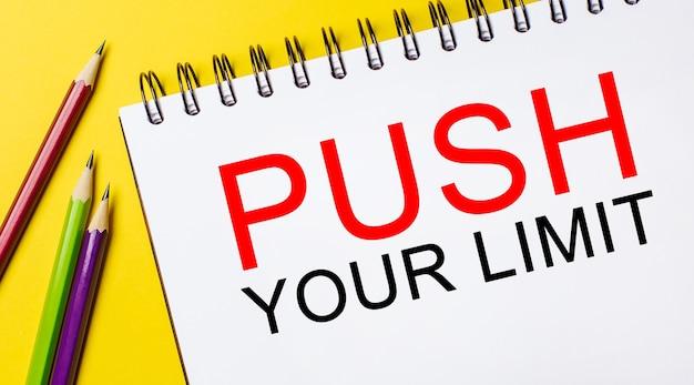 Spingi il tuo limite su un blocco note bianco con matite su sfondo giallo. concetto di affari
