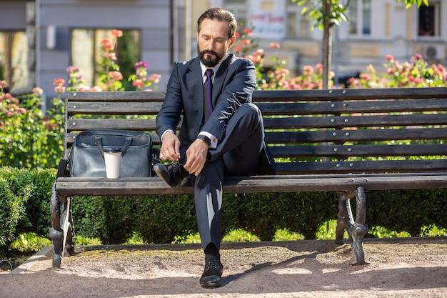 Mettere in ordine. piacevole imprenditore impegnato seduto sulla panchina mentre si allaccia le scarpe
