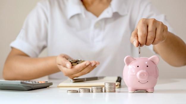 Mettere le monete dei soldi nel salvadanaio risparmiando denaro