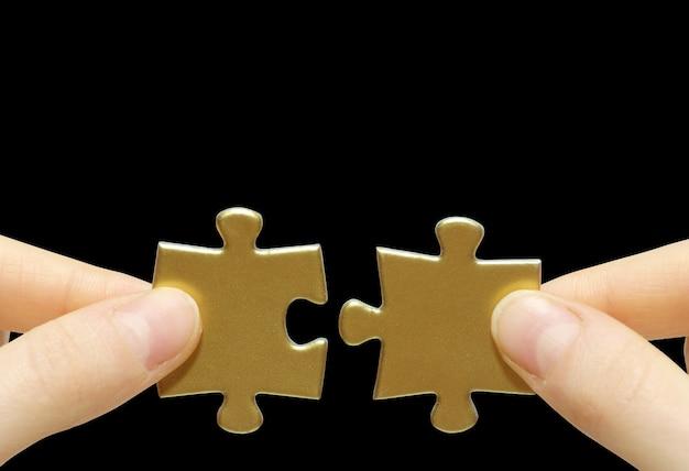 Puzzle in mano isolato sul muro nero