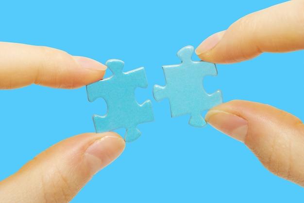 Puzzle in mano isolato sull'azzurro