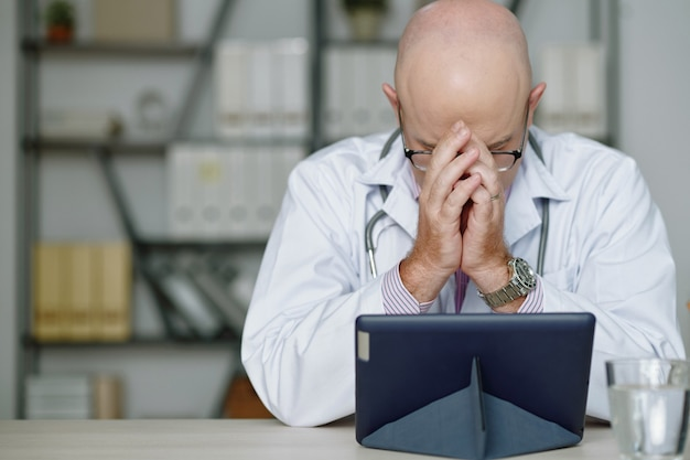 Medico caucasico calvo perplesso in camice bianco stanco dal lavoro seduto al tavolo e coprendo il viso con le mani durante la lettura delle informazioni sul tablet in ufficio