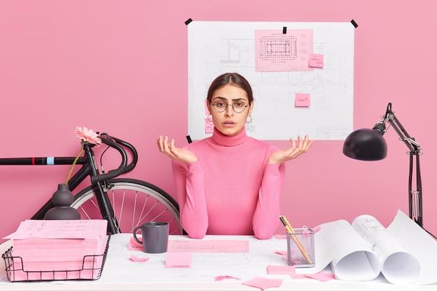 Perplesso deluso impiegato donna europea allarga le palme creat grafica si sente confuso indossa occhiali rotondi dolcevita pose nello spazio di coworking ha progetti e schizzi sul desktop