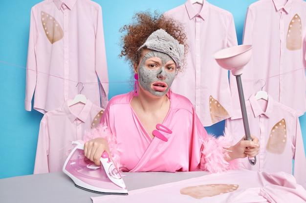 La donna dispiaciuta perplessa si preoccupa della carnagione applica la maschera di argilla sul viso indossa la vestaglia e la benda sulla fronte tiene lo strumento per la pulizia fa le faccende domestiche stira la biancheria vicino al bordo