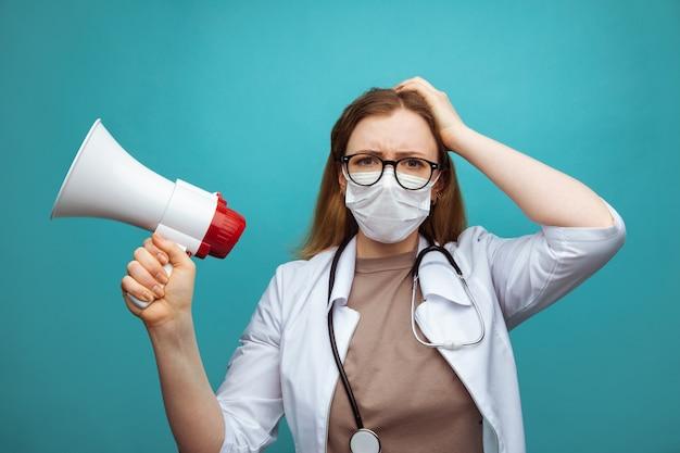 Medico femminile perplesso nella maschera di protezione dell'abito medico isolata sull'azzurro