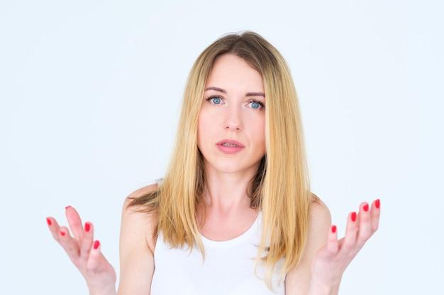 Donna scioccata perplessa con diffusione sul muro bianco.