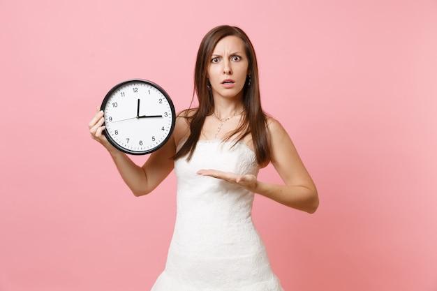 Donna perplessa in abito bianco di pizzo che indica la mano sulla sveglia rotonda
