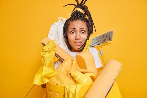 Giovane donna afroamericana preoccupata perplessa sopraffatta dalla pulizia