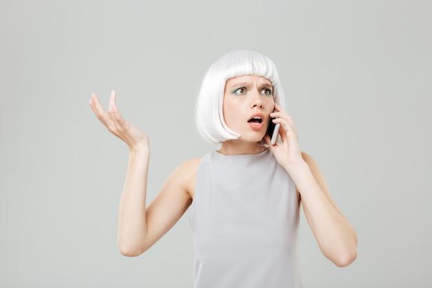 Giovane donna preoccupata perplessa in parrucca bionda in piedi e parlando al cellulare mobile