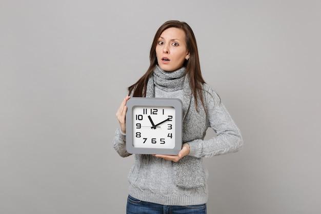 Perplesso giovane donna in maglione grigio, sciarpa tenere orologio quadrato isolato su sfondo grigio, ritratto in studio. stile di vita sano, persone sincere emozioni, concetto di stagione fredda. mock up copia spazio.