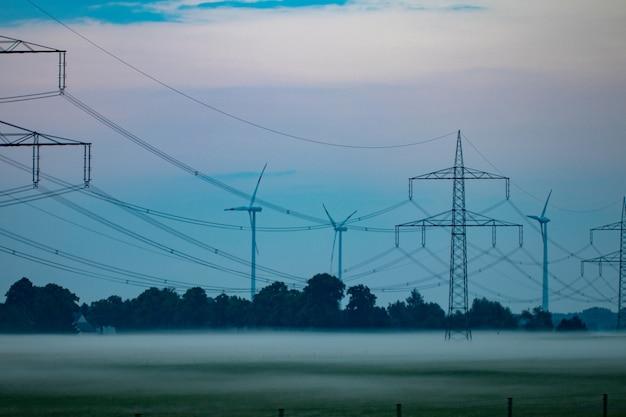 Pilone e linea elettrica di trasmissione nel tramonto.